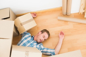 Image of man lying on the floor with boxes on top of him